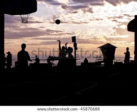 streetball player silhouettes at laguna beach california. taking a shot. - stock photo