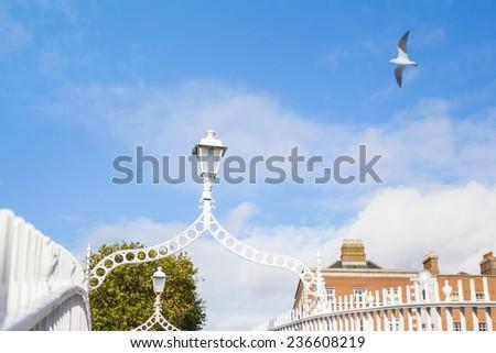 Streetlight on Hapenny Bridge against blue sky in Dublin, Ireland - stock photo