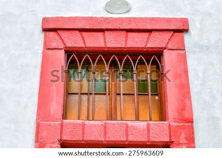 Streets and buildings of Mala Strana quarter in Prague: red window with iron bars - stock photo