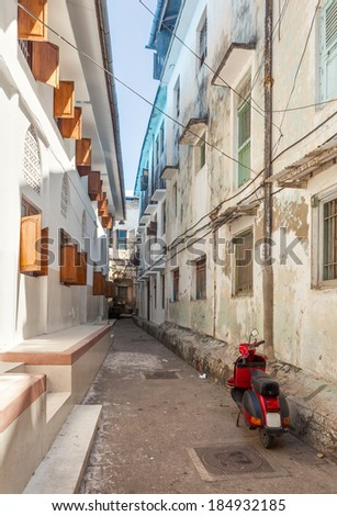 Streets in heart of Stone Town city, which mostly consists of a maze of narrow alleys lined by houses, shops, bazaars and mosques. Most streets are too narrow for cars. Located in Zanzibar, Tanzania. - stock photo