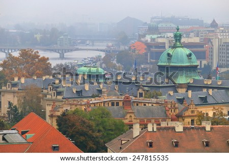Streets of Prague and distant bridges across Vltava river in foggy autumn day, Czech Republic - stock photo
