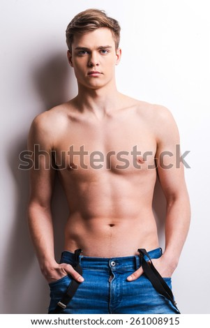 Strength and masculinity. Handsome young muscular man holding hands in pockets while standing against grey background - stock photo