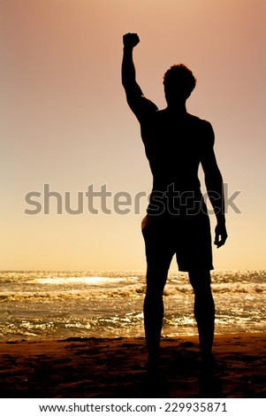 Strength man in front of the sea feeling power - stock photo