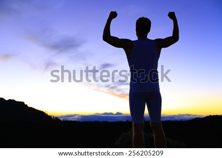 Strength - strong success fitness man flexing muscles showing power pose outside in silhouette at night. Muscular fit male fitness man celebrating success macho style. - stock photo