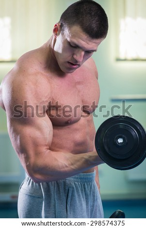 Strength training bodybuilder. Training with dumbbells.