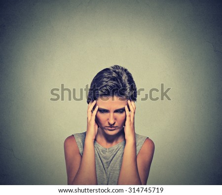 Stress. Closeup young woman stressed with headache. Female stressed and worried with migraine headache pain - stock photo