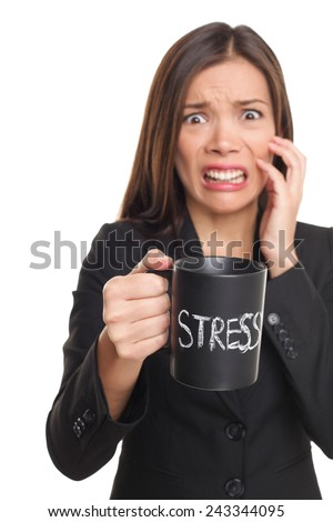 Stress concept. Business woman stressed being too busy. Businesswoman in suit holding head drinking coffee creating more stress. Mixed race Asian Caucasian female isolated on white background. - stock photo