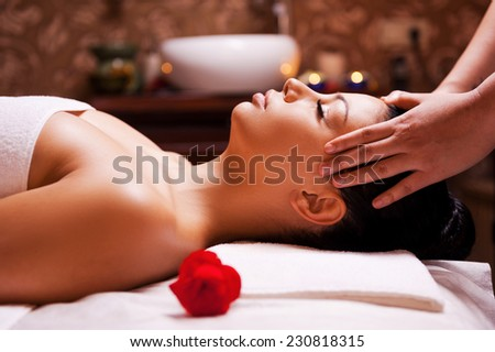 Stress removing. Side view of beautiful young woman lying on back while massage therapist massaging her head  - stock photo