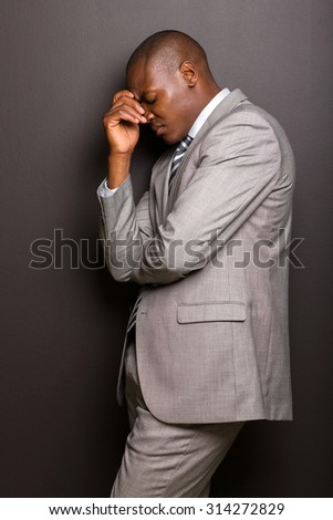 stressed african american man standing against black background - stock photo
