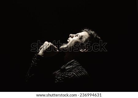 Stressed, aggressive, frustrated portrait of a young student, man,screaming holding his fists up isolated on black background.Facial expression - stock photo