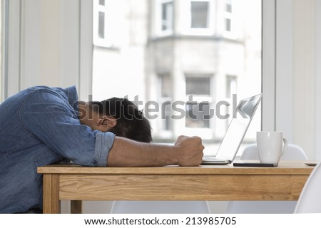 Stressed and frustrated Asian man sitting at his laptop. - stock photo