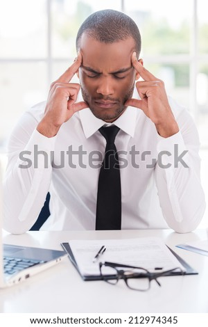 Stressed and tired. Depressed young African man in formalwear holding head in hands and keeping eyes closed while sitting at his working place - stock photo