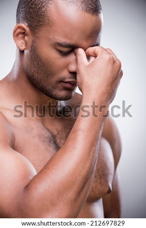 Stressed and tired. Portrait of shirtless African man touching his nose and keeping eyes closed while standing against grey background