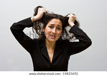 Stressed and worried business woman, grabbing and pulling her hair, isolated on a white background - stock photo