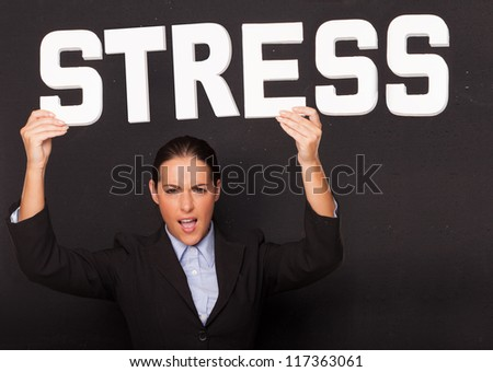 Stressed angry attractive businesswoman holding up the word STRESS in white lettering high above her head on a black studio background - stock photo