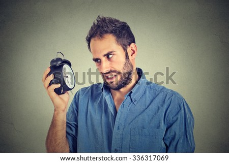 Stressed annoyed man with alarm clock. It is too early for that meeting  - stock photo