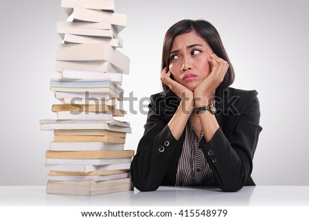 Stressed Asian female worker sitting at her desk and looking at a pile of books on her side - stock photo