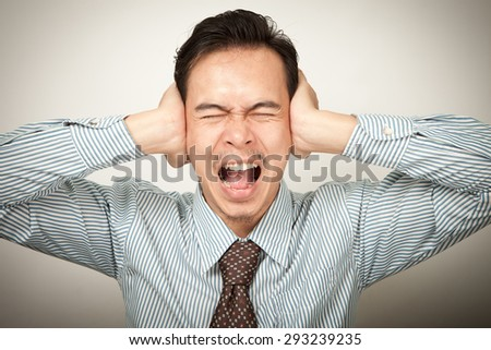 stressed  asian man covering closed ears looking at you, don't want to listen or headache. - stock photo