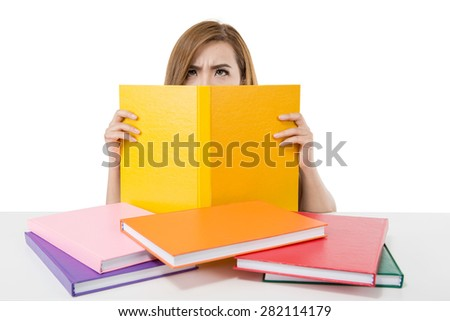 Stressed Asian student girl behind stack of books - stock photo