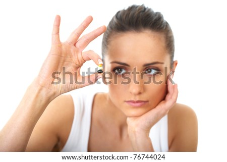 stressed attractive young brunette holds some pills in her hand, isolated on white - stock photo