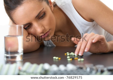 stressed attractive young brunette with some pills and glass of water - stock photo