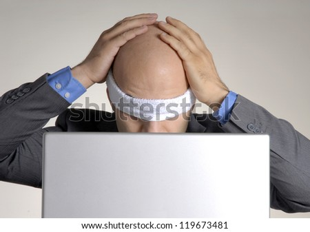 Stressed blindfolded bald man working on computer. - stock photo
