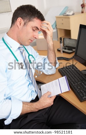Stressed British GP sitting at desk - stock photo