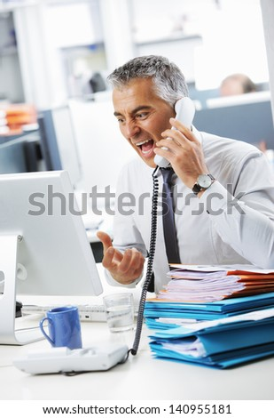 Stressed business man shouting at phone in office - stock photo