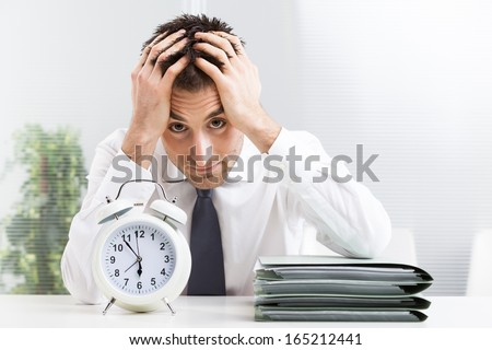 Stressed business man under time pressure cries in office - stock photo