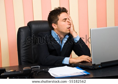 Stressed business man with problems on laptop holding  face in his hand - stock photo