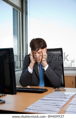 Stressed business manager sitting at his desk - stock photo