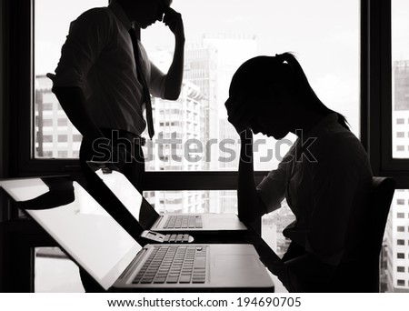 Stressed business woman and business man in the office. - stock photo