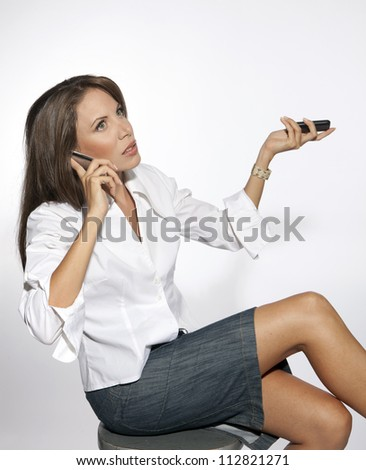 Stressed business woman in the office using two phones simultaneously - stock photo