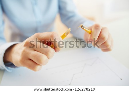 Stressed business worker releasing tension by breaking a pencil - stock photo