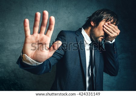 Stressed businessman after business project failure, covering eyes in despair and hand gesturing stop to camera. - stock photo