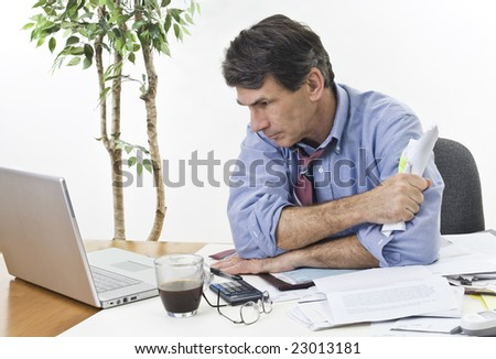 Stressed businessman at his office laptop, trying to find the best direction for his company. - stock photo