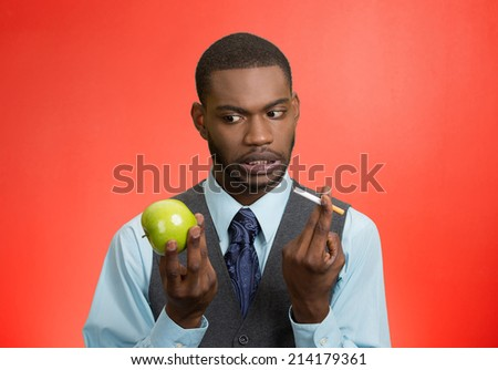 Stressed businessman deciding on healthy life choices, craving cigarette versus green apple isolated red background. Face expression, body language, bad, hazardous human habits - stock photo