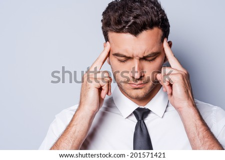 Stressed businessman. Frustrated young man in shirt and tie touching head with fingers and keeping eyes closed while standing against grey background - stock photo