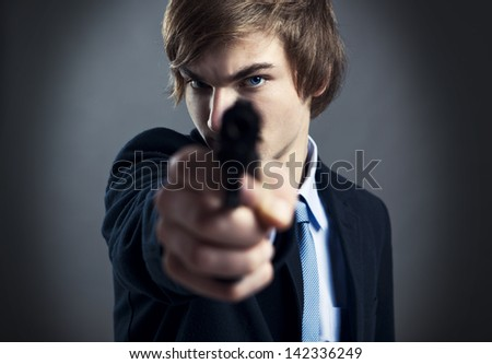 Stressed businessman holding and pointing a gun to the camera - stock photo