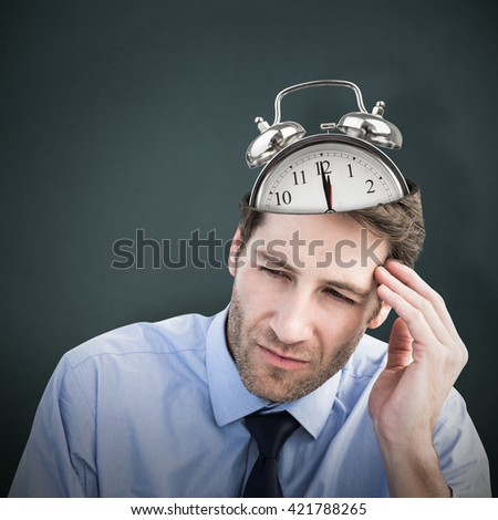 Stressed businessman holding his head against teal, blue background