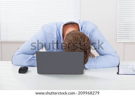 Stressed businessman leaning on desk with laptop in office - stock photo