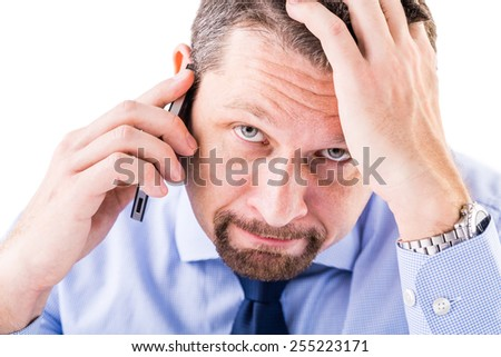 Stressed businessman making a phone call. - stock photo