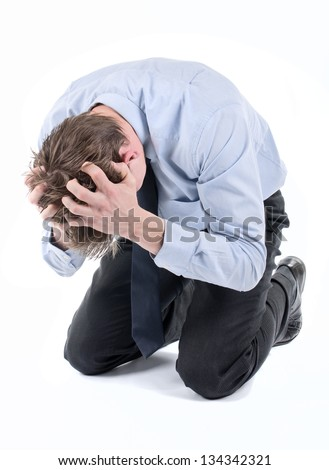 Stressed businessman on his knees with hands in hair