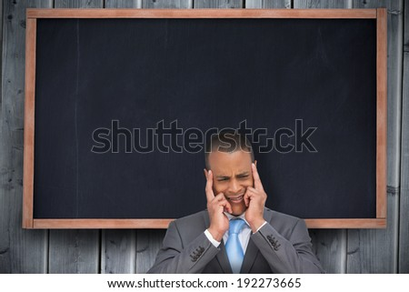 Stressed businessman putting his fingers on his temples against chalkboard on grey wooden planks - stock photo