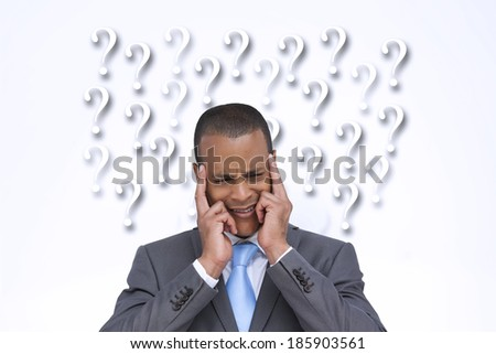 Stressed businessman putting his fingers on his temples against question marks - stock photo