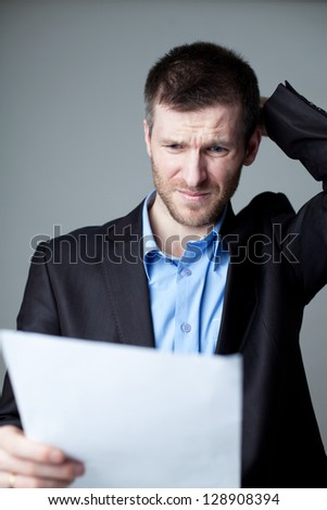 Stressed businessman reading document.