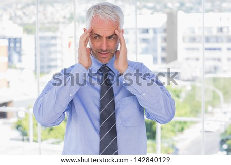 Stressed businessman rubbing his temples in his office - stock photo
