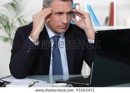 Stressed businessman sat at desk - stock photo