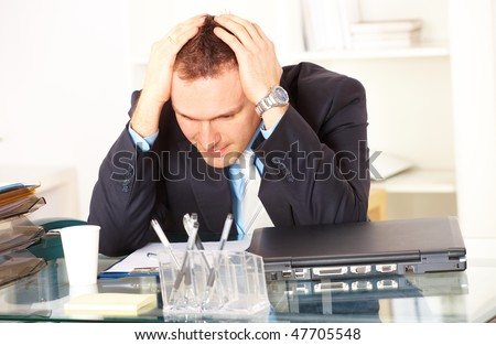 Stressed businessman sitting at desk holding his head and worrying