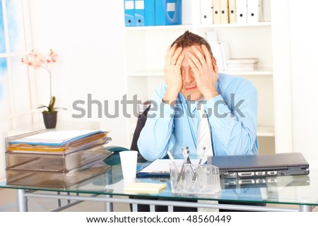 Stressed businessman sitting at desk holding his head and worrying - stock photo